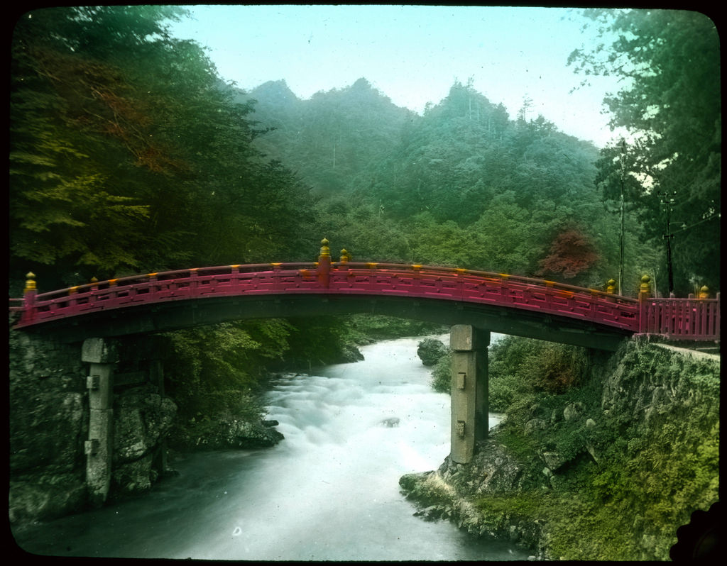 Curved red wooden bridge over river; for by UVicLibraries, on Flickr