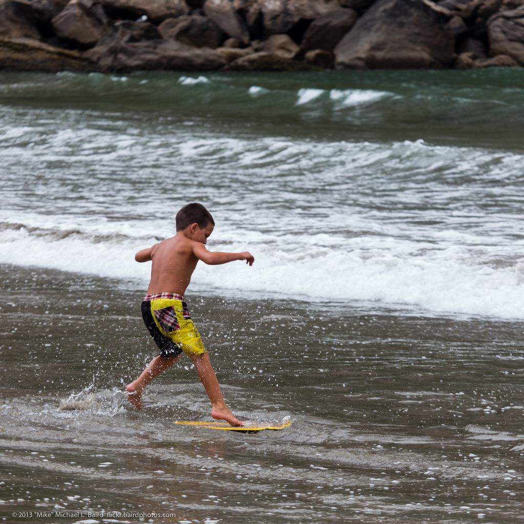 Young boy skim boards at water's edge. by mikebaird, on Flickr